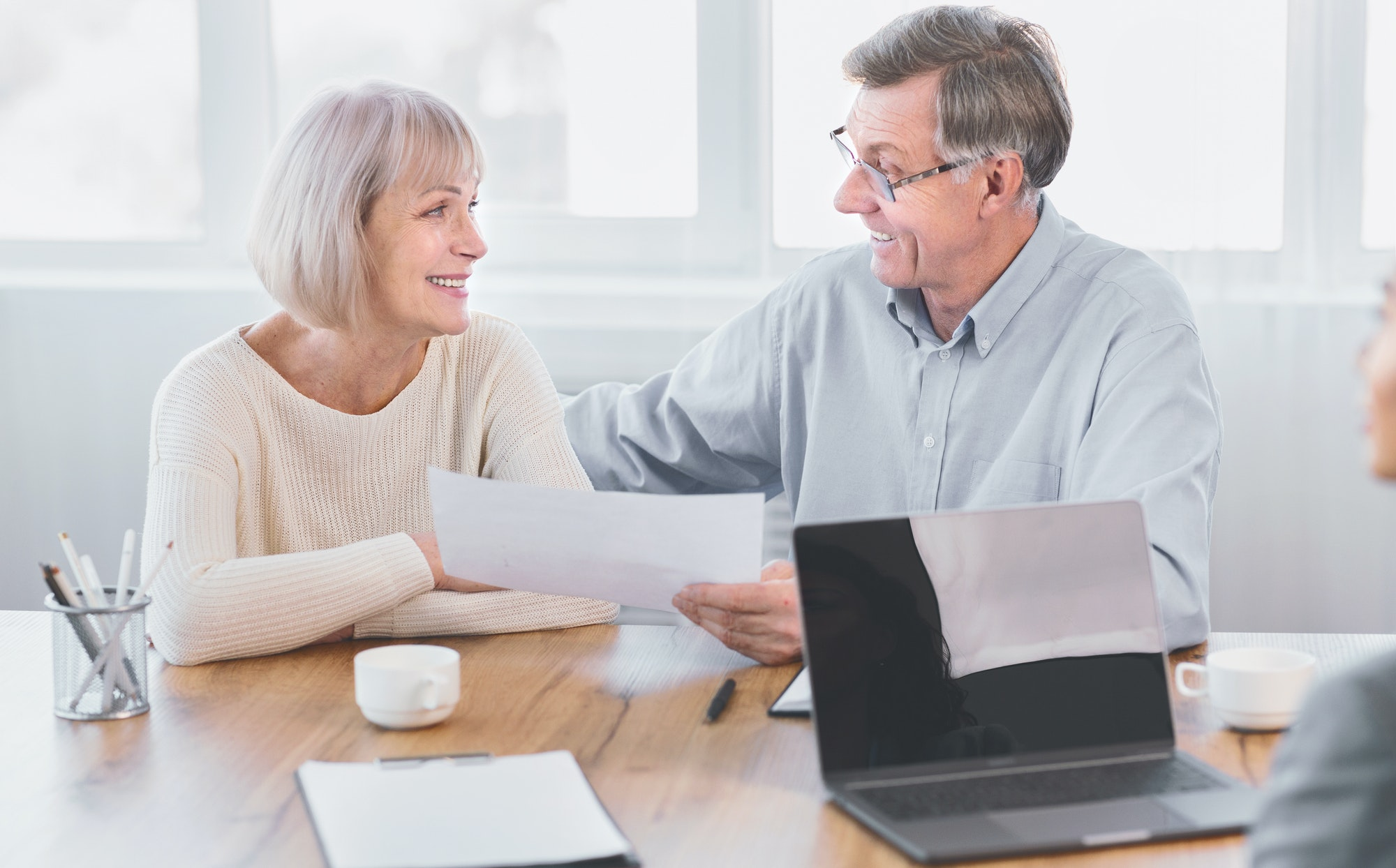 Mature couple talking to financial advisor at office